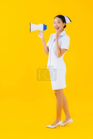Photo for Portrait beautiful young asian woman thai nurse with megaphone for communicate in clinic and hospital on yellow isolated background - Royalty Free Image