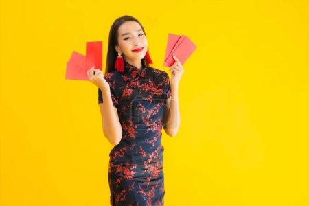 Photo pour Portrait belle jeune femme asiatique porter robe chinoise avec Ang Pao ou lettre rouge avec de l'argent pour la nouvelle année chinoise concept sur fond isolé jaune - image libre de droit