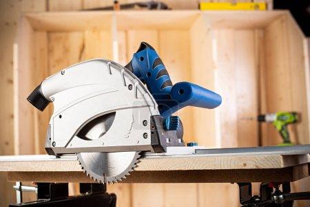 Photo pour Scie circulaire à main avec morceau de bois sur établi. gros plan de scie machine à bois outil de construction concept meubles faisant fond bricolage - image libre de droit