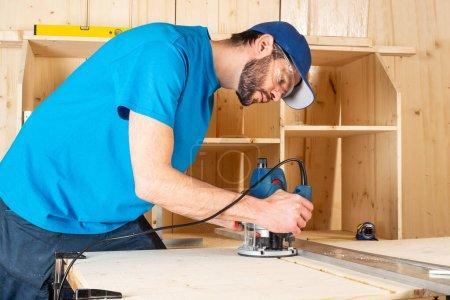 Photo pour Menuisier avec routeur à bois manuel au travail. gros plan de routage d'une fente dans la planche de pin outil de construction de travail du bois meubles concept faisant fond bricolage - image libre de droit