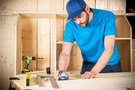 Photo pour Jeune menuisier avec barbe et ruban à mesurer au travail. mesure sur planche de bois construction bois outil concept meubles fabrication bricolage fond - image libre de droit