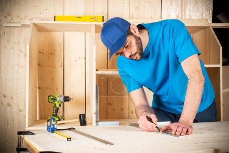 Photo pour Jeune menuisier avec crayon barbe et compteur d'angle d'arrêt au travail. mesure sur planche de bois construction bois outil concept meubles fabrication bricolage fond - image libre de droit