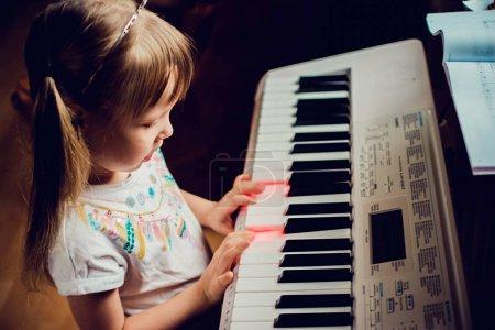 Photo pour Petite fille jouant un synthétiseur - image libre de droit