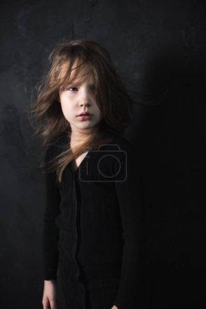 Foto de Retrato de la niña linda posando en la luz del sol en el fondo oscuro del estudio, de cerca - Imagen libre de derechos