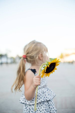 Photo for Cute little girl in summer dress holding bright yellow sunflower while standing at street - Royalty Free Image