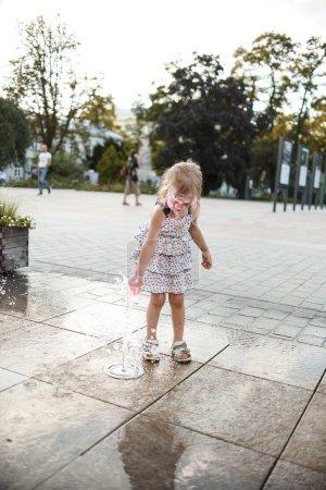 Photo pour Mignonne petite fille s'amuser tout en jouant dans la flaque d'eau à la rue - image libre de droit