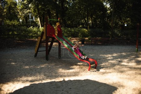 Foto de Chica linda deslizándose por el tobogán en el patio de recreo en el día soleado de verano - Imagen libre de derechos