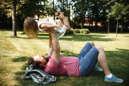 Foto de Padre con hija pequeña divirtiéndose mientras jugaba en hierba verde en el parque de verano - Imagen libre de derechos