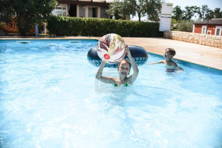 Photo pour Fille retenant la bille de plage près du garçon avec le cercle gonflable tout en jouant dans la piscine - image libre de droit