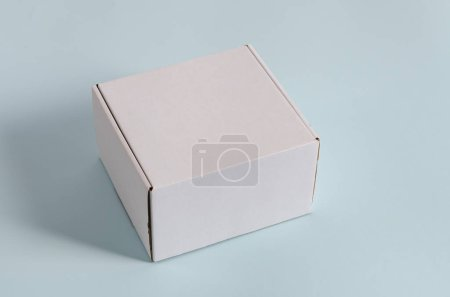 Photo for White gift box. Blank gift box on blue background with shadow. Copy space, side view - Royalty Free Image