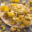 Dried chamomile flowers in a wooden spoon on a gra...