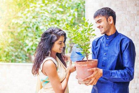 Photo pour Beau couple indien arrosant la plante dans le jardin sur leur balcon à la maison - image libre de droit