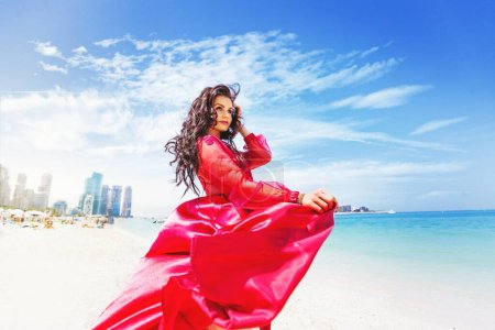Photo for Beautiful young woman in a fancy dress standing on a Jumeirah beach Dubai, UAE - Royalty Free Image