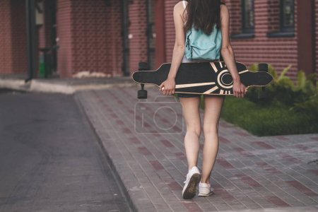 rear view of girl with long hair holding long board on city street