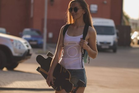 girl with long hair holding long board on city street
