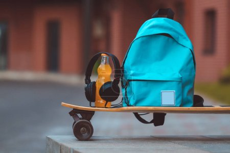 Blue backpack standing on long board with headsets and bottle with beverage
