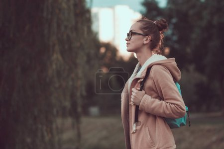 thoughtful girl in hood with backpack standing in city park in rainy weather