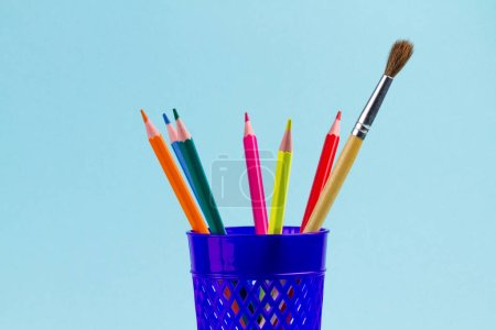 Colourful stationery, school supplies in blue cup on blue background.