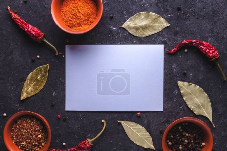 Photo for Frame for text of spices, red, dried peppers, bay leaves on dark background. Copy space. - Royalty Free Image
