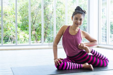 Photo for Beautiful Asian woman wearing sportswear, striped pants, playing yoga in the room, feeling relaxed, happy and healthy. - Royalty Free Image