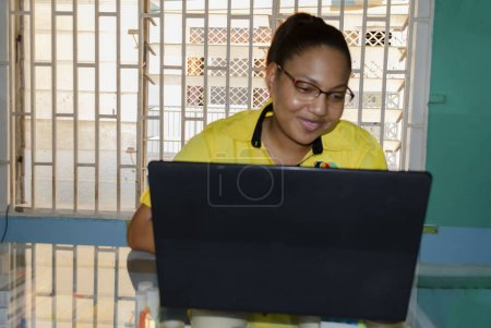 Bright, pleasant, smiling face of female viewing her black laptop through the lense of a pair of tested lens of her burgundy and grey glasses. The lady is of light skin complexion, thin, pink lips, and fat nose. She wears yellow and black shirt.