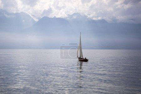 Photo pour Paysage du lac Léman avec un bateau à voile et les Alpes en arrière-plan - Vevey, Suisse - image libre de droit
