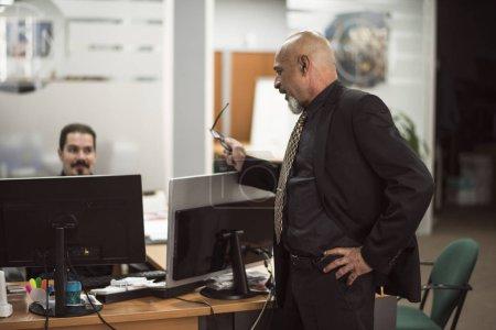 Photo pour Homme chauve aîné travaillant dans le bureau avec le costume noir taliking avec le commis - image libre de droit