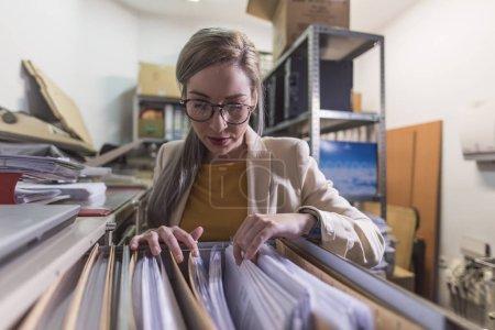 Photo pour Grand angle de femme de bureau attrayante travaillant des dossiers de regard dans le sous-sol - image libre de droit