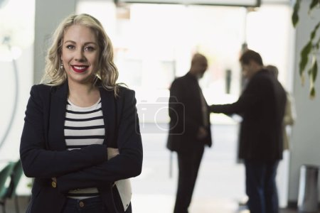 Photo for Office woman looking at camera and smiling with people in background - Royalty Free Image