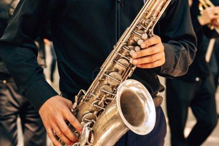 Photo pour Un mec en tenue noire joue du saxophone. Musicien de rue. Promenade le long de la rue Arbat dans la ville de Shymkent. Festival des fleurs au Kazakhstan . - image libre de droit