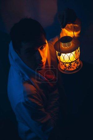 Photo pour Homme avec lampe jaune décorative dans l'obscurité. - image libre de droit