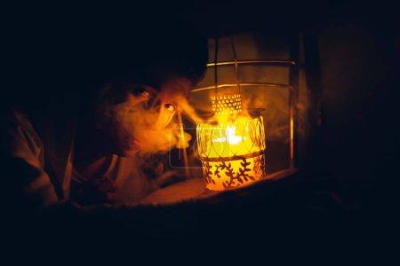 Photo pour Homme avec lampe jaune décorative dans l'obscurité. foyer doux - image libre de droit
