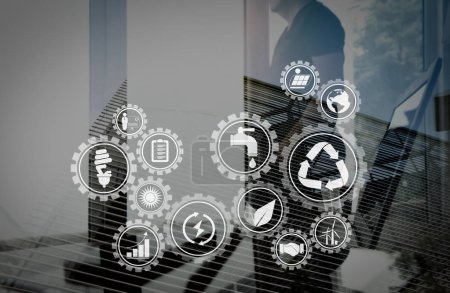 Sustainable development with icons of renewable energy and natural resources preservation with environment protection inside connected gears.Double exposure of businessman working with new modern computer