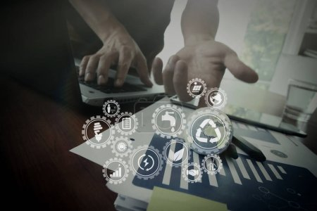 Sustainable development with icons of renewable energy and natural resources preservation with environment protection inside connected gears.businessman showing texture world on business document.