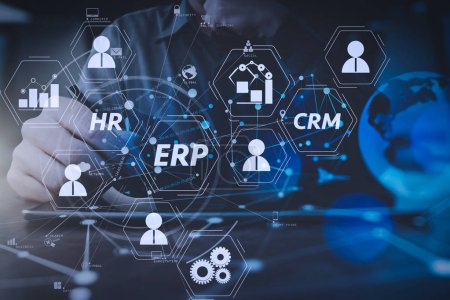 Photo for Architecture of ERP (Enterprise Resource Planning) system with connections between business intelligence (BI), production, CRM modules and HR diagram.businessman hand working with modern digital tablet computer. - Royalty Free Image