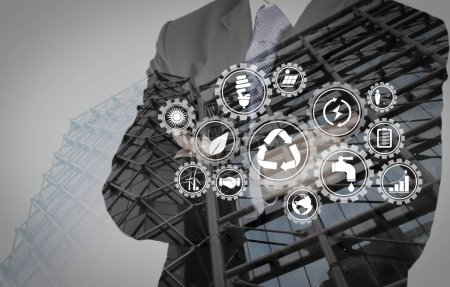 Sustainable development with icons of renewable energy and natural resources preservation with environment protection inside connected gears.Double exposure of success businessman with abstract building.