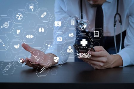 Modern VR with medical technology diagram concept.close up of smart medical doctor working with smart phone and stethoscope on dark wooden desk