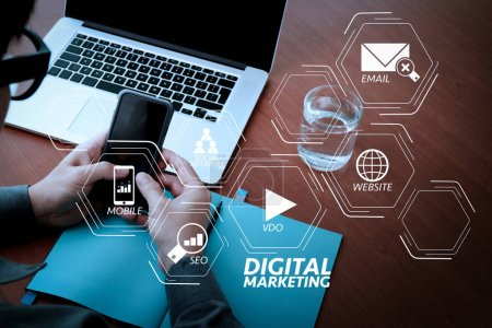 Photo for Digital marketing media (website ad, email, social network, SEO, video, mobile app) in virtual screen.businessman hand working with mobile phone and modern computer and business strategy as concept - Royalty Free Image
