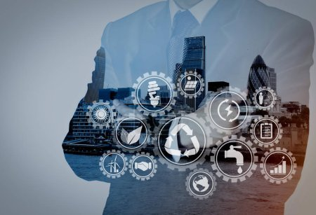 Sustainable development with icons of renewable energy and natural resources preservation with environment protection inside connected gears.Double exposure of success businessman with abstract building