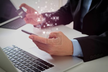 Social media and Marketing virtual icons screen concept.businessman making credit card purchase online with mobile phone and laptop computer on modern desk