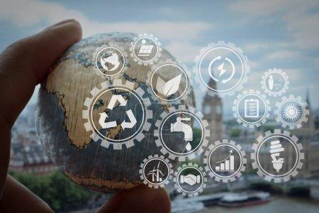 nachhaltige Entwicklung mit Symbolen der erneuerbaren Energien und der Erhaltung natürlicher Ressourcen mit Umweltschutz innerhalb vernetzter Getriebe. Geschäftsmann Hand zeigt Textur der Welt mit digitalen sozialen Medien-Netzwerk.
