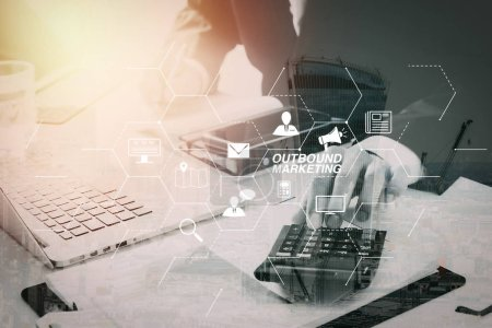 Outbound marketing business virtual dashboard with Offline or interruption marketing.businessman hand working with finances about cost and calculator and latop with mobile phone on withe desk in modern office.