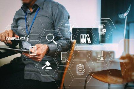 Compliance virtuelles Diagramm für Vorschriften, Gesetze, Normen, Anforderungen und Audit.Geschäftsmann arbeitet mit digitalem Tablet und Laptop-Computer und Kartenanhänger im modernen Büro.