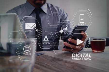 Photo for Digital marketing media (website ad, email, social network, SEO, video, mobile app) in virtual screen.success businessman hand using smart phone,digital tablet docking smart keyboard,coffee cup on wooden desk - Royalty Free Image