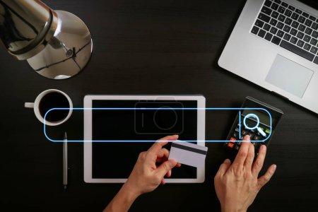 Foto de Búsqueda Navegación Internet Data Information Networking Concept with blank search bar.Internet shopping concept.Vista superior de las manos que trabajan con ordenador portátil y tarjeta de crédito y tableta en mesa de madera oscura - Imagen libre de derechos