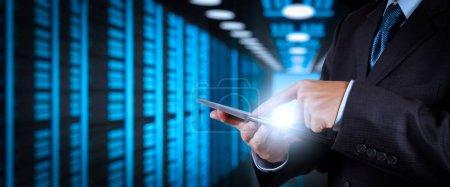 Photo pour Homme d'affaires travaillant avec VR ordinateur grand écran vierge sur la salle des serveurs en arrière-plan . - image libre de droit