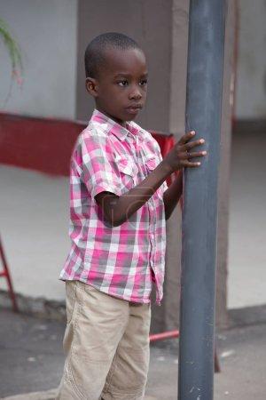 Photo pour Enfant, triste et solitaire, debout dans la rue contre un métal - image libre de droit