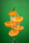 Fresh Orange Slices Tossed in Air With water