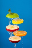 Wet Slices of Fresh Fruit Tossed in Air with water