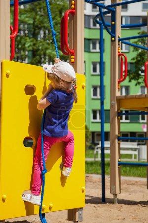 Photo pour Petite fille active sur l'aire de jeux - image libre de droit